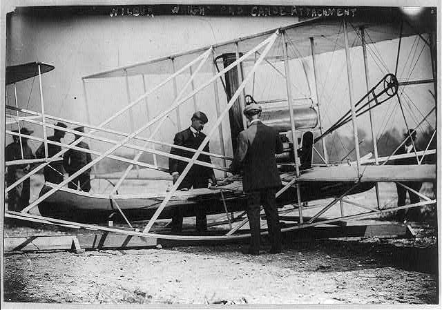 Wilbur Wright examining canoe attachment to aeroplane before 1st flight over water