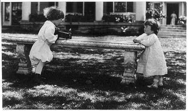 [One child aiming camera, on bench, at another child, Washington, D.C.]