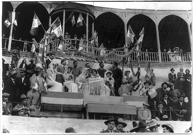 Bull fight, Mexico: guests of honor, surrounded by Mexican flags, watching bull fight