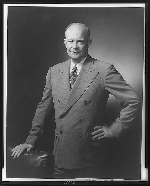 [Dwight D. Eisenhower, three-quarter length portrait, standing, facing slightly left, hand on back of chair]