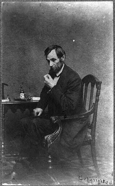 [Abraham Lincoln, seated next to small table, in a reflective pose, May 16, 1861]