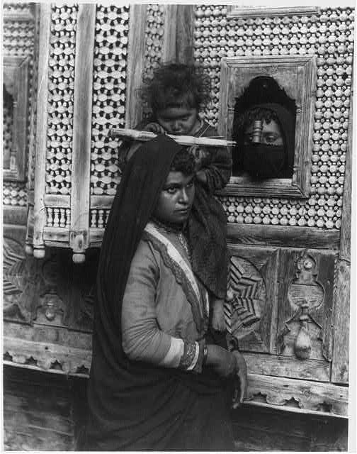 [Child, who is blind in one eye, seated on shoulder of woman and sucking sugar cane; and head of another woman looking through window, Egypt]