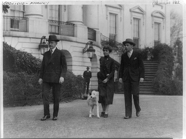 [Pres. and Mrs. Calvin Coolidge, their son, John, and dog, walking outside the White House?]