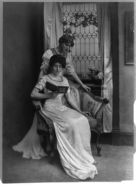 [Miss Jessie Wilson, standing, and Miss Eleanor R. Wilson, seated, reading]