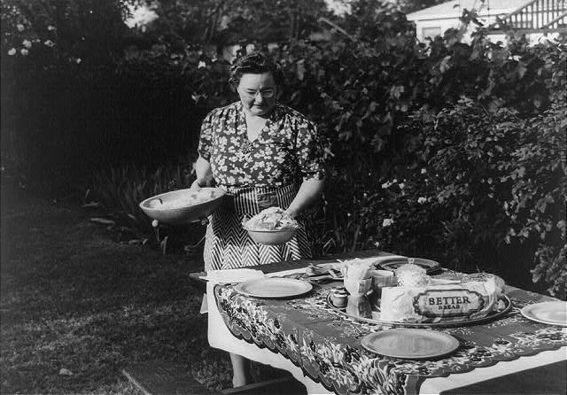 Turlock, California. Housewife serves dinner in the backyard of her home. Menu: barbecued steaks, fresh peas, potato salad, potato chips, celery and olives, strawberry shortcake, and coffee