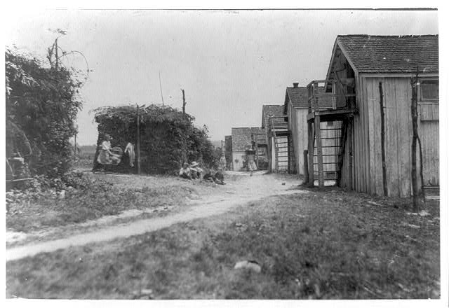 Shanties and cooking shacks on berry farm of Bottomley's, near Baltimore. Md. At times, four families live in one shanty: three families is the rule--two rooms. (See report July 10, 1909.)  Location: Baltimore, Maryland.