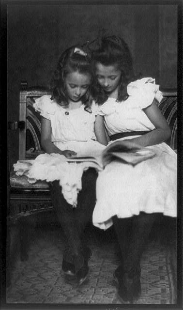 [Two girls wearing white dresses and dark stockings reading a book]