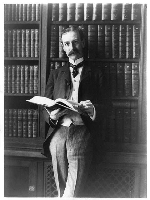 [Herbert Putman, three-quarter-length portrait, standing, facing left, in library, holding book]