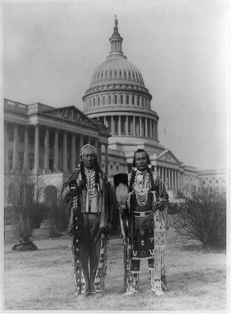 [Native American chiefs Frank Seelatse and Chief Jimmy Noah Saluskin of the Yakama tribe posed, full-length portrait, standing, facing front, with the U.S. Capitol behind them]
