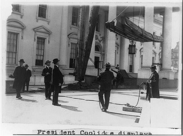 President Coolidge displays great interest in the progress of the work being done on the White House