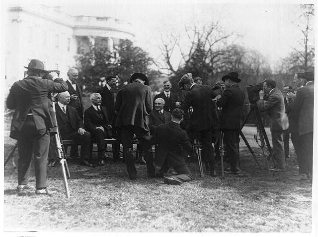 [President Warren G. Harding and his cabinet posed on the White House Lawn, with photographers]