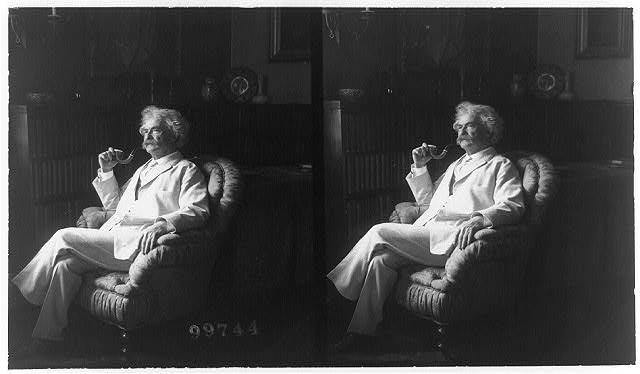 [Samuel Clemens, full-length portrait, seated, facing left, smoking pipe]