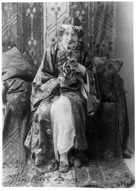 [Neith Boyce Hapgood,full-length portrait, seated facing front, wearing ornamental costume and holding roses]