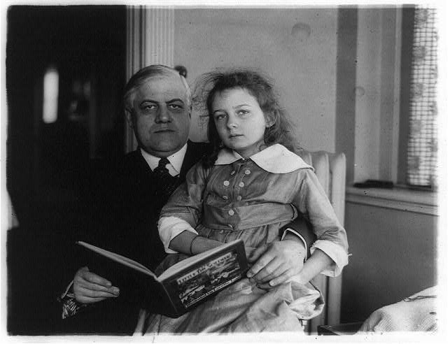 [Alexander Mitchell Palmer, three-quarter-length portrait, seated facing front, with girl on his lap, holding book]