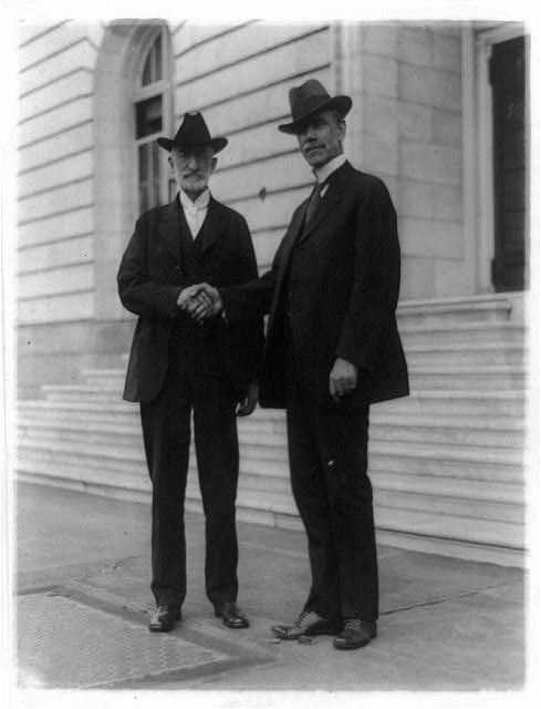 [Heber Jeddy Grant (1856-1945) left, standing and shaking hands with Reed Smoot (1862-1941) outside Senate office building]