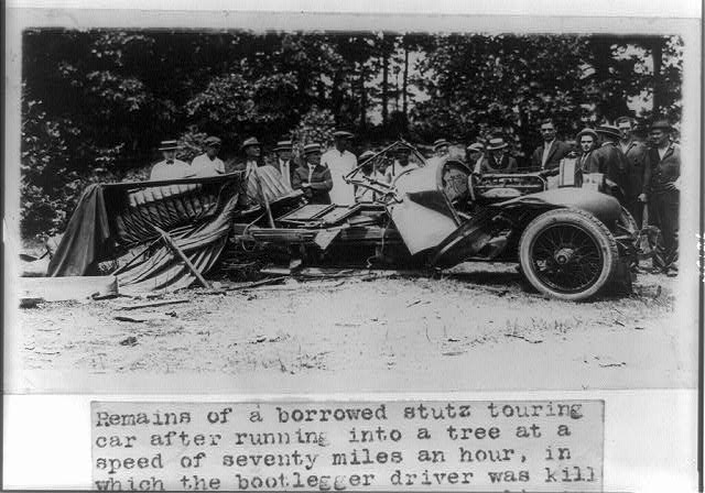 Remains of a borrowed Stutz touring car after running into a tree at seventy miles an hour, in which the bootlegger driver was killed and fifty gallons of corn liquor was destroyed and confiscated