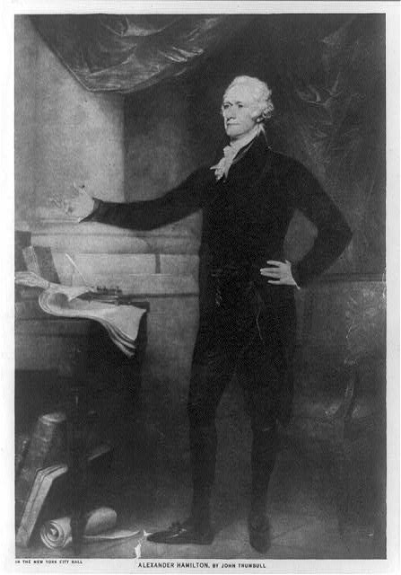 [Alexander Hamilton, full-length portrait, standing, facing left, left hand on hip, right arm extended outward, books and papers beside him]