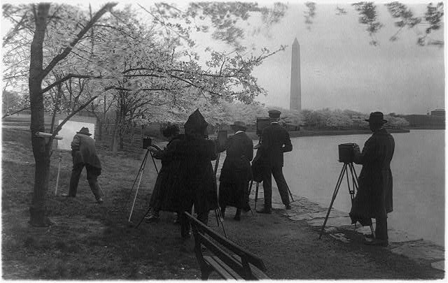 [Man with easel and group of photographers at the Tidal Basin facing the Washington Monument in the background, with cherry trees in blossom, Washington, D.C.]