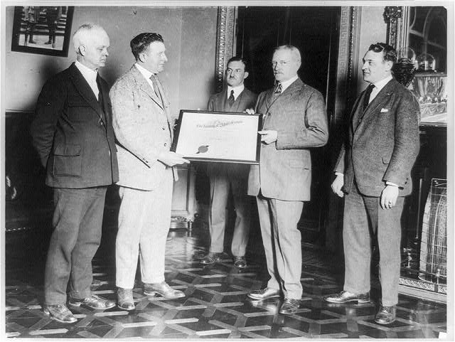 [John J. Pershing and another man holding certificate of Nobility of Almas Temple, with three other men standing around them]