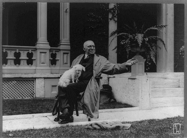 [James Whitcomb Riley, full-length portrait, seated, facing right, with dog upon his lap, waving goodbye, on sidewalk in front of porch]