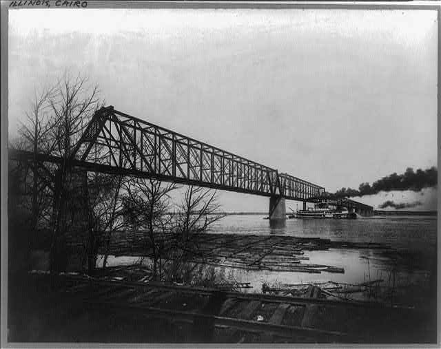 [Stern-wheel riverboat passing under Illinois Central Railroad bridge over Ohio River, Cairo, Illinois, with logs lashed together at river's edge]