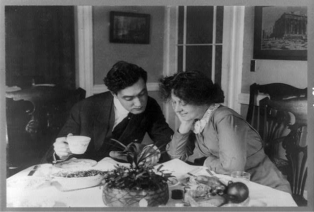 [Edgar Selwyn and Margaret Mayo Selwyn seated at table reading together]