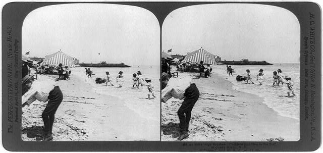 An extra large breaker. Children paddling in the surf at Coney Island, N.Y.