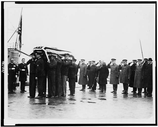 America's highest dignitaries of state, army and navy stand at salute while the casket containing the body of the unknown soldiers is borne to the casson [sic] taking it from the Navy Yard to the Capitol. In the group are General Pershing, Gen. Lejeune, commander of the Marine Corps, Gen. Harbord and others