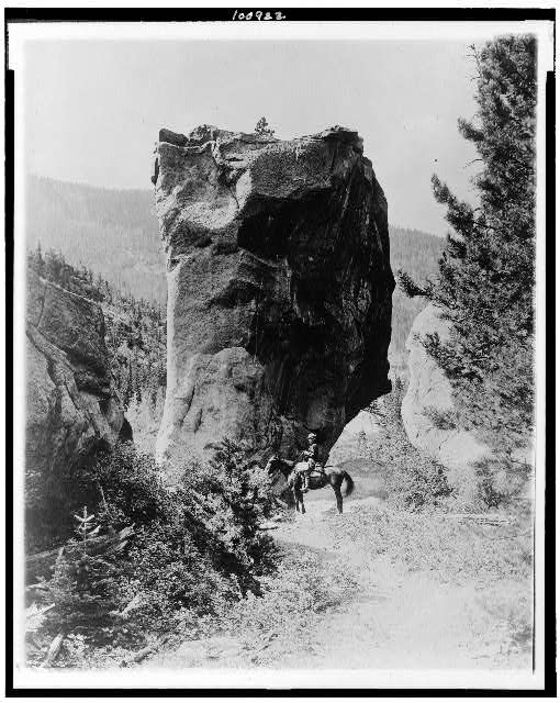 [Man on horseback by butte in Rocky Mountain National Park, Colorado]