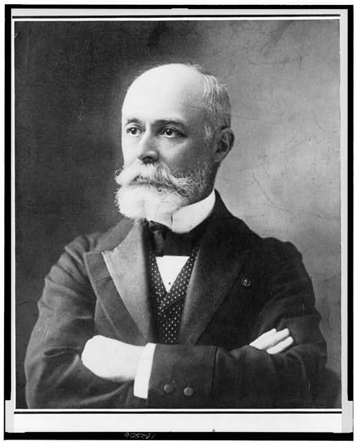 [Henri Becquerel, head-and-shoulders portrait, facing left, with arms folded across chest]