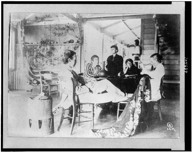 [Robert Louis Stevenson with his family sitting around table at home in the Hawaiian Islands]