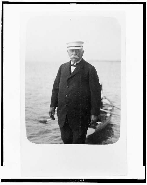 [Count Ferdinand von Zeppelin, three-quarter length portrait, standing, facing front, with small boat behind him]