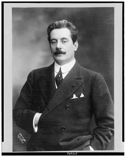 [Giacomo Puccini, half-length portrait, standing, facing slightly left, right hand inside coat]