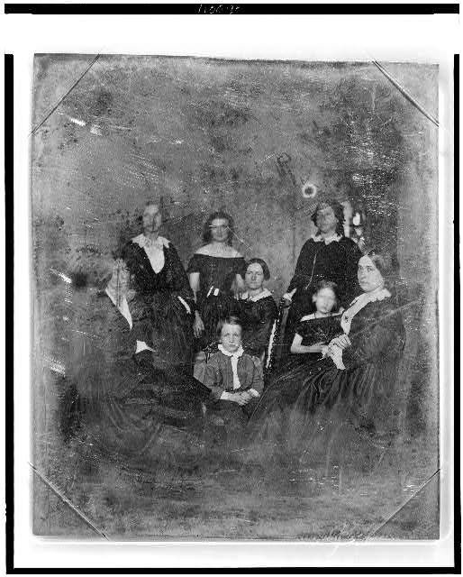 [Unidentified group of six women and a boy and girl, three women and the boy are seated in chairs]