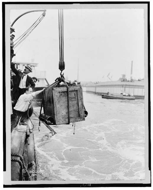 [Crate containing Harry Houdini, being lowered from ship into water]