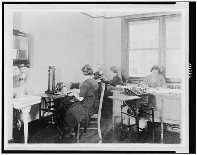 [Three young women at work in an unidentified Washington, D.C. office. The girl at the left is operating an addressograph]. Washington D.C. [Photograph]
