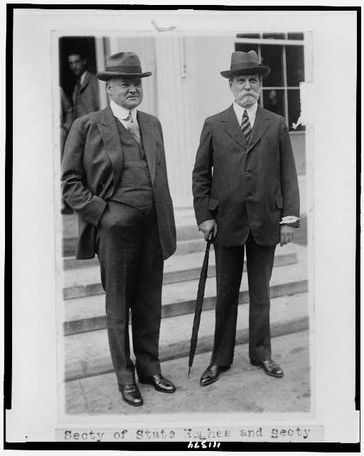 [Secretary of State Charles Evans Hughes and Secretary of Commerce Herbert Hoover, full-length portraits, standing, outside of building]