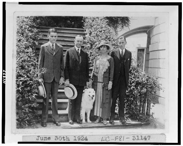 [President and Mrs. Coolidge, full-length portraits, standing on steps, with their two sons and their pet dog]