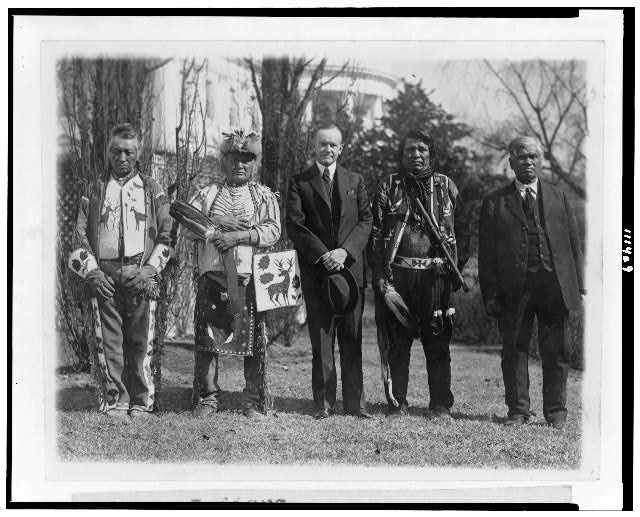 [President Calvin Coolidge posed with Natives, possibly from the Plateau area in the Northwestern United States, near the south lawn of the White House]