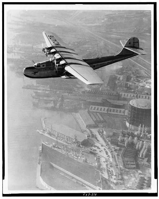"[Aerial view of Pan American Airways ""China Clipper"" over Grove(?) Street Municipal Terminal, Oakland, California]"