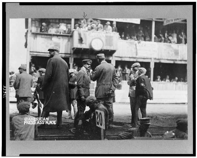 [William Kissam Vanderbilt, II, full-length, standing on track for automobile race, facing right, with crowd in grandstand in background]