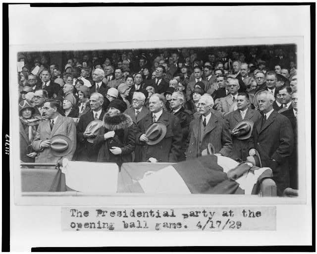 [Herbert Hoover and presidential party standing, with men holding their hats, at opening baseball game]