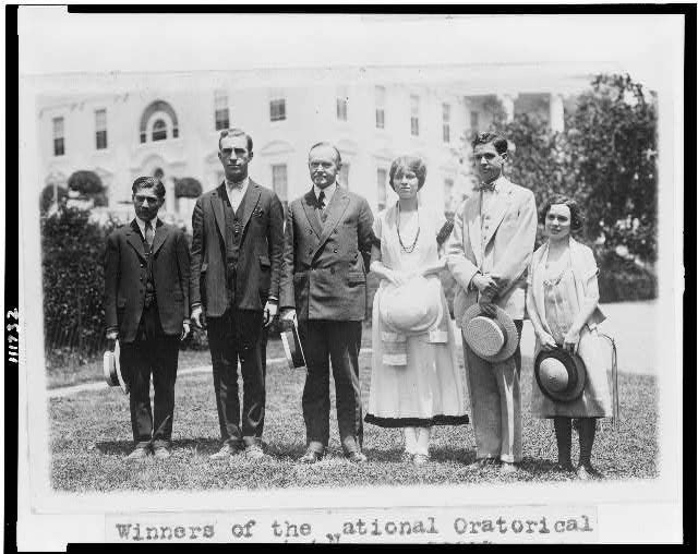 [President Coolidge, full-length portrait, standing, facing slightly left, with five members of the national oratorical contest]