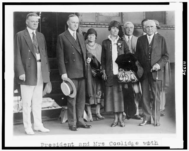 [President and Mrs. Coolidge standing, full-length portrait, with Secretary of Commerce Herbert Hoover and Secretary of State Frank B. Kellogg, at Union Station, on their return from Swampscott]