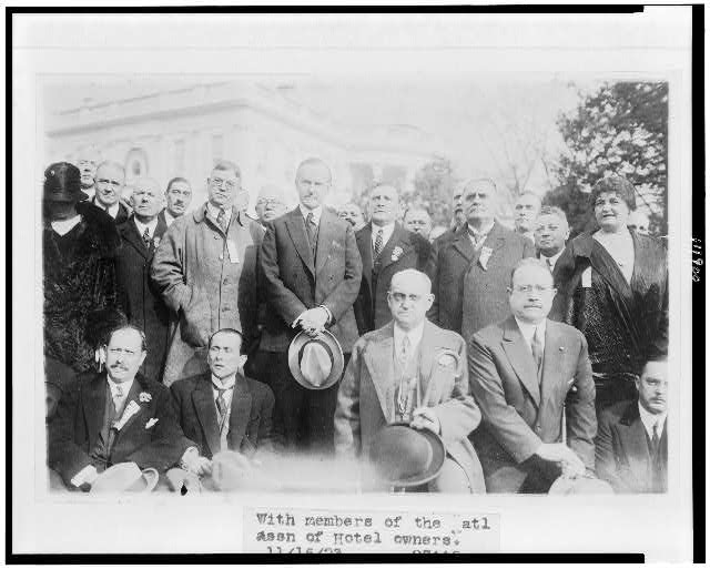 [President Coolidge standing with members of the National Association of Hotel Owners, on the White House lawn]