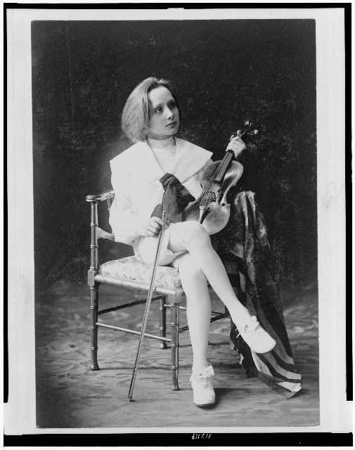 [Boy, seated, full-length, facing right, holding violin and bow]