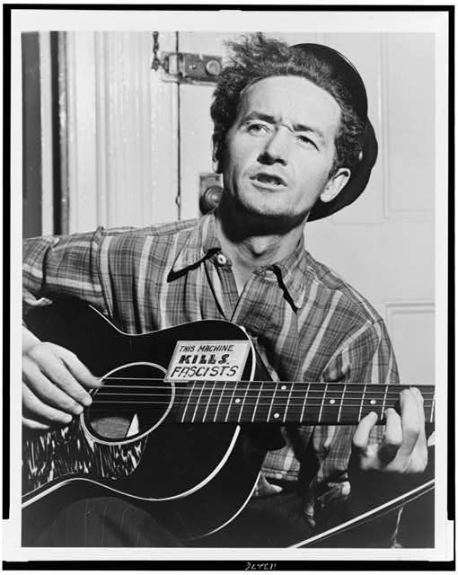 [Woody Guthrie, half-length portrait, facing slightly left, holding guitar]