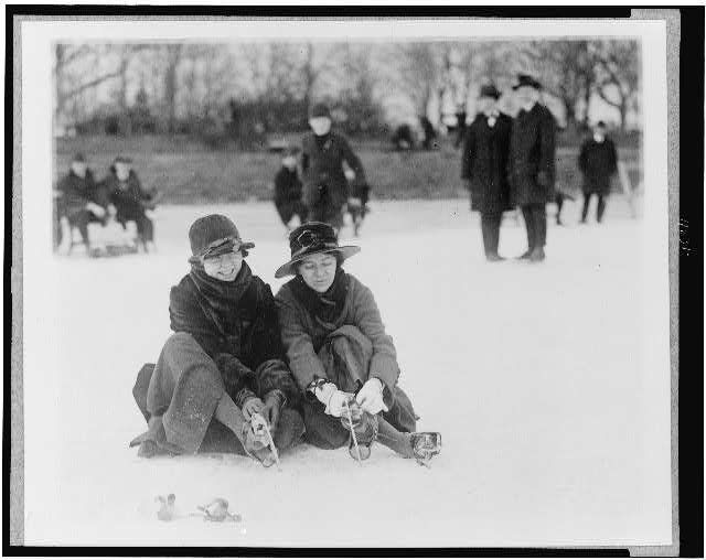 [Two people seated on snow, and putting on ice skates, in the Washington, D.C., area]