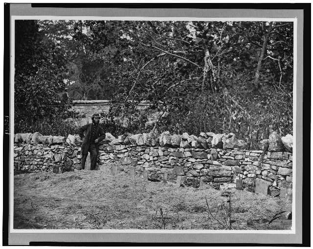 [Soldier standing at graves of Federal soldiers, along stone fence, at Burnside Bridge, Antietam, Maryland]