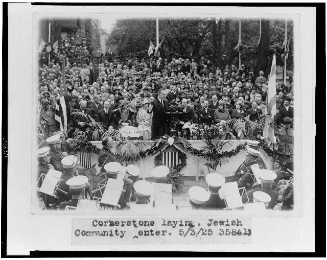 [Calvin Coolidge speaking at cornerstone laying, at the Jewish Community Center, Washington, D.C.(?), with band in foreground, and visitors in background]